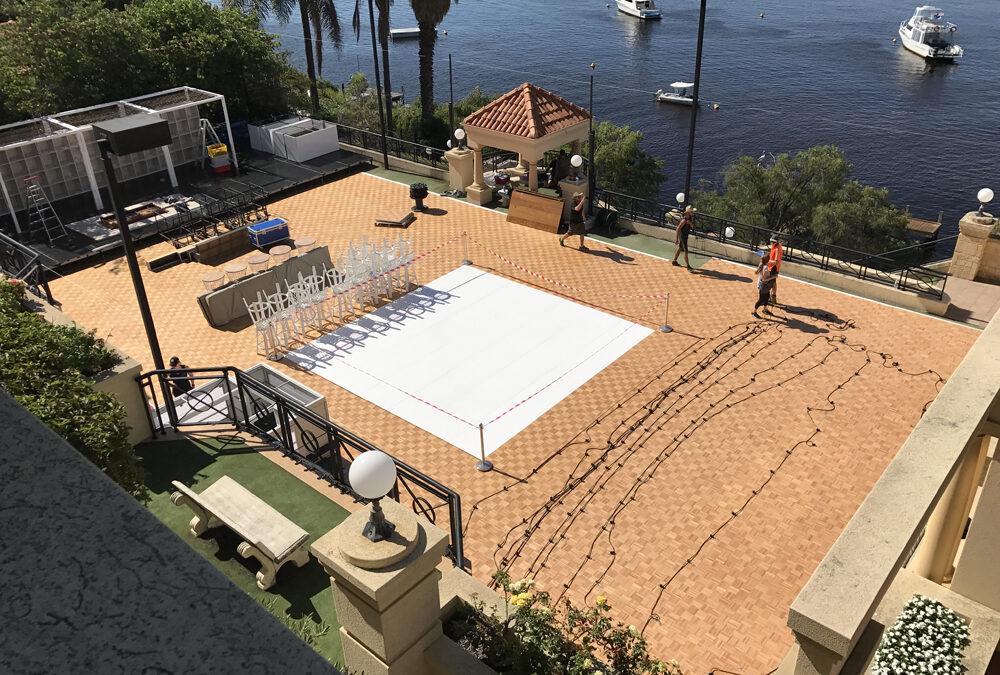 Parquetry dance floor on tennis court with white gloss dance floor insert
