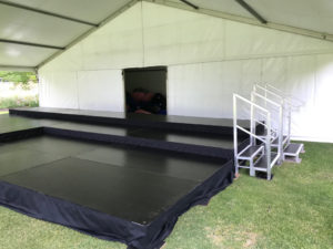 Stage on uneven ground under marquee