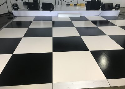 White gloss stage and checker board dance floor.
